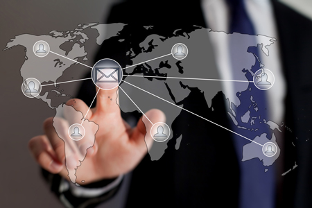 Picture of man placing finger of global map with emails being sent to world.