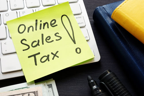Online sales tax note on a keyboard with money nearby.