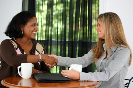 Two women shaking hands in a meeting maker tactics conference