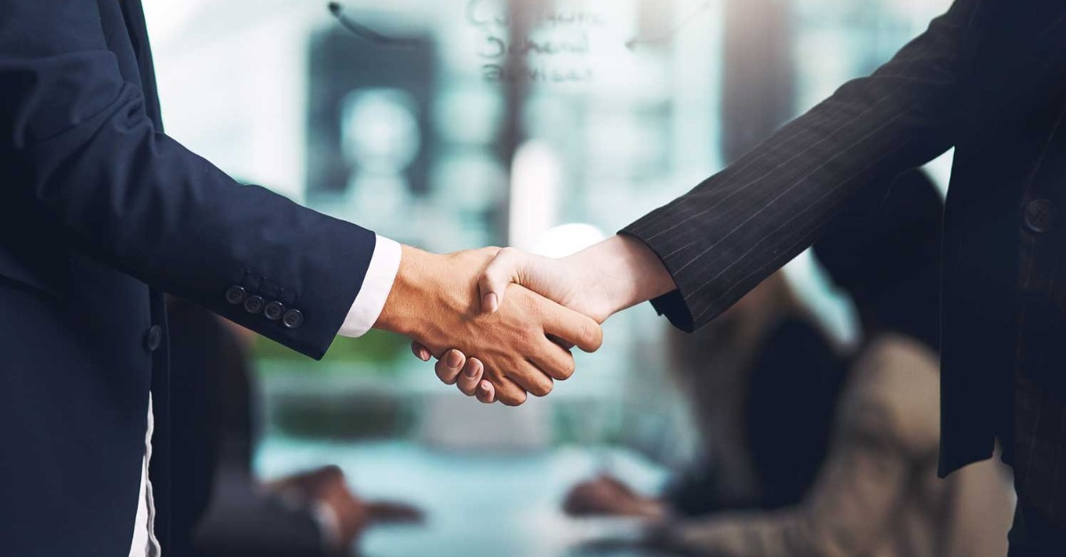 Female and male business people shaking hands after agreeing to new email sending platform contract.